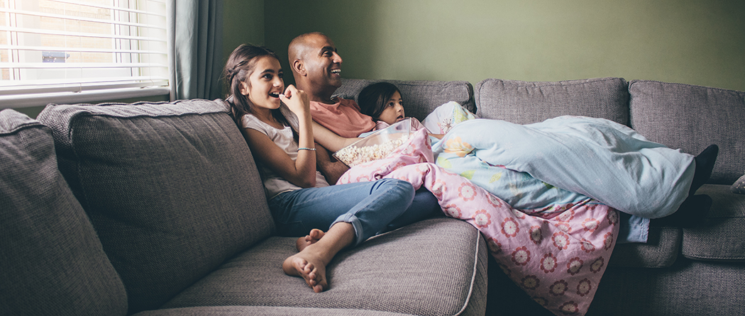father and daughters enjoy family movie night