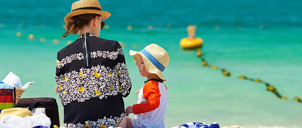 Two year old toddler boy in sun hat with mother on beach practicing healthy skin habits at the beach to prevent skin cancer