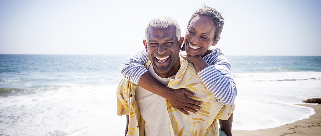 A senior couple enjoys a day at the beach after using life insurance as part of their retirement investment plan