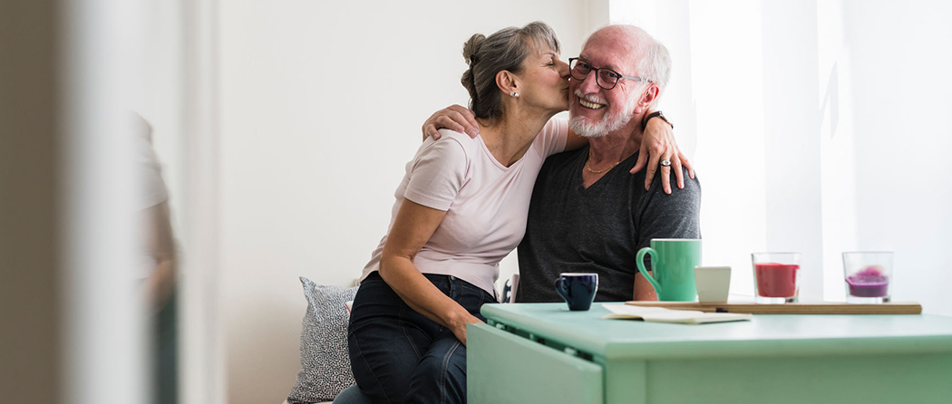 A senior couple drink coffee and talk about saving for retirement after they maxed out their 401k