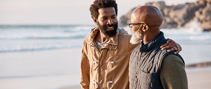 A senior man talks to a younger man about naming him as his life insurance beneficiary.